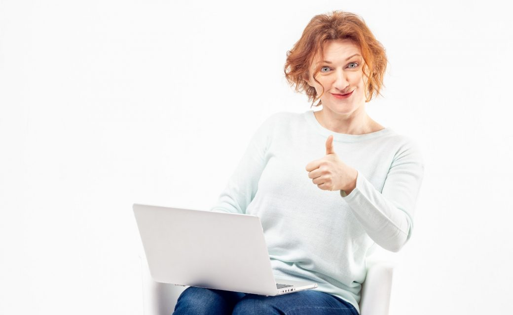 Portrait of mature woman with content or satisfied expression on her face with a laptop and thump up