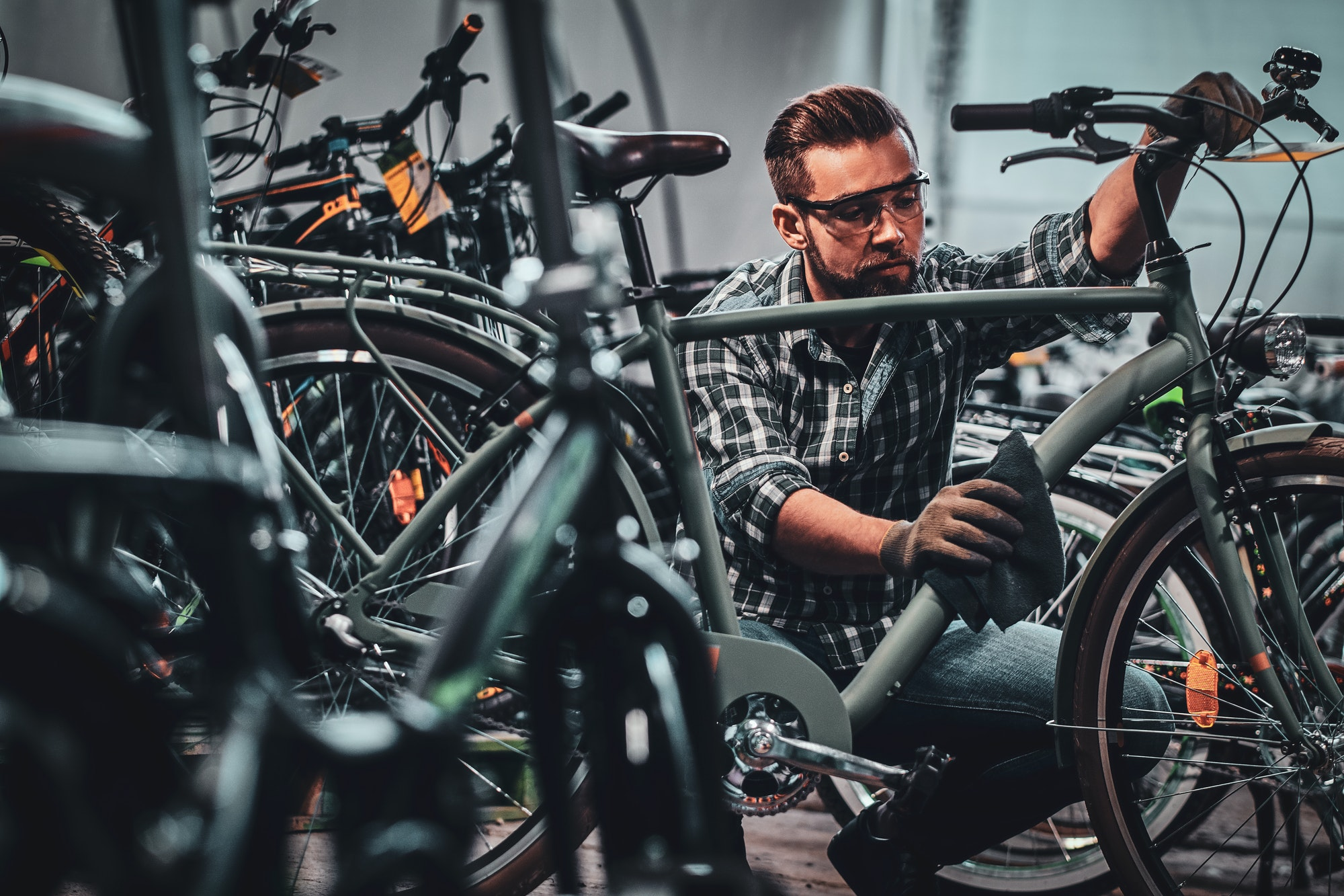 Busy attractive man in protective glasses is cleaning bicycle from dirt