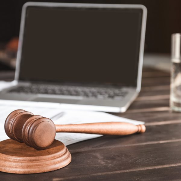 brown wooden judge hammer and documents with laptop behind, law concept